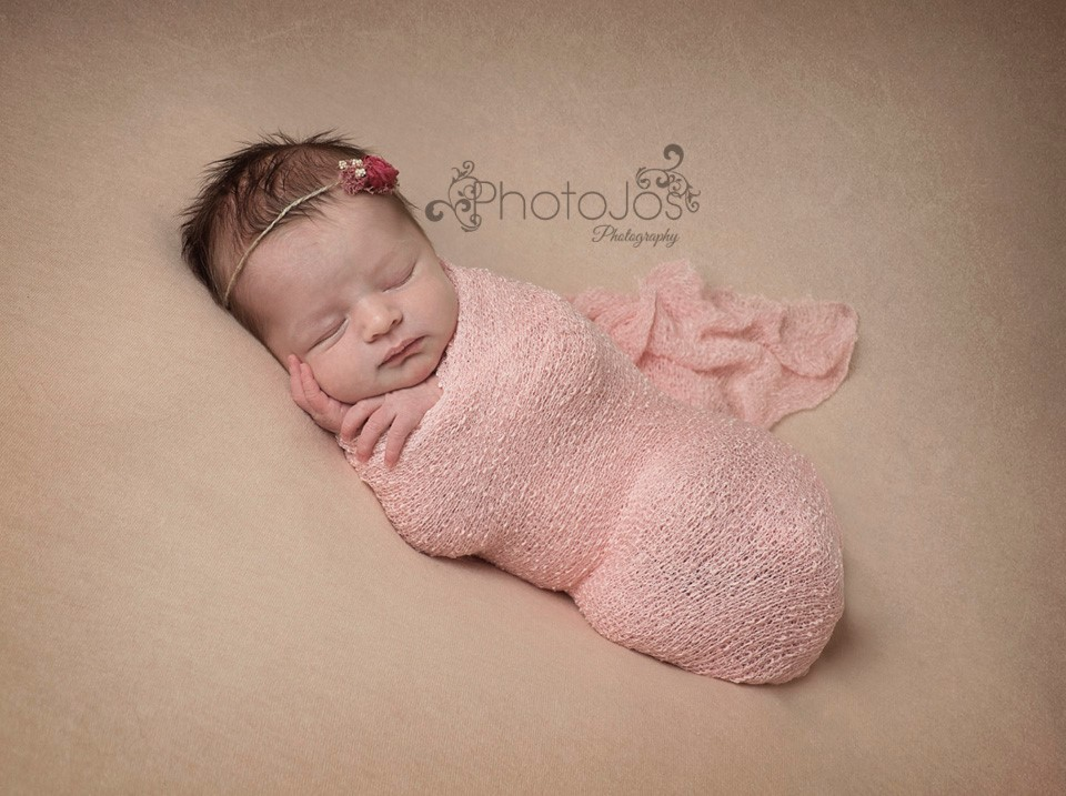 Baby wrapping baby in pink